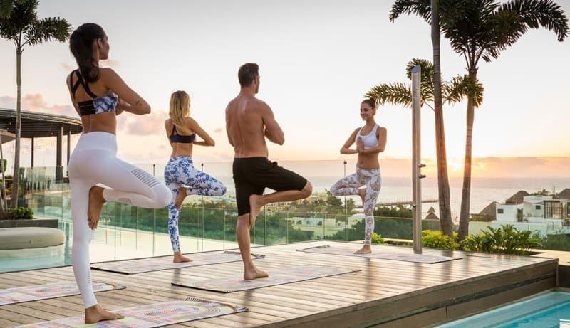 Personas relajandose haciendo yoga en la playa.